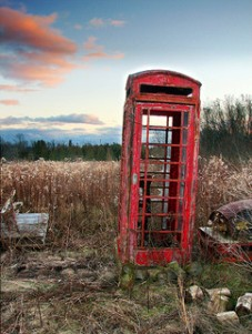 Red phone booth in fileld